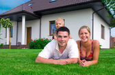 Happy family in front of the house — Stok fotoğraf