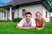 Voorkant van het huis en gelukkige familie — Stockfoto