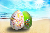 Colorful easter eggs on sunny beach — Stock Photo
