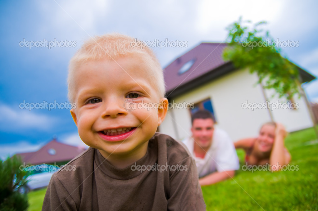 Happy child in front of the house with parents in the background  Photo #2045182