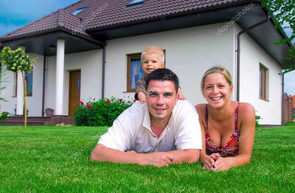 Happy family having fun in front of their house — Stock Photo #2045195