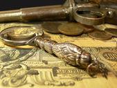 Magnifying glass, coins, gun — Stock Photo