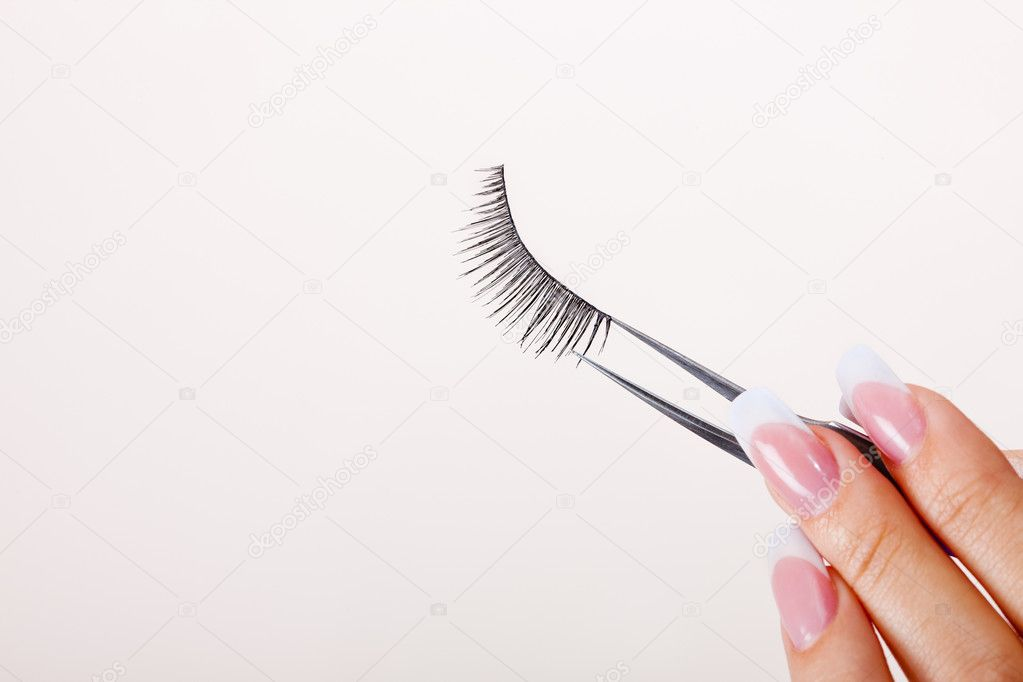 Woman hand holding false eyelashes in pincers — Stock Photo #1732734