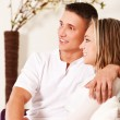 Smiling couple sitting on sofa — Stockfoto