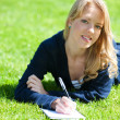 Stock Photo: Pretty girl studying on a green meadow