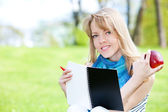 Pretty girl studying on a green meadow — Stock Photo