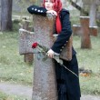 Gothic girl with a rose on a cemetery — Stock Photo