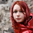 Redhead girl in with red satin cloak — Stock Photo