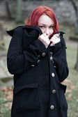 Redhead flirty goth girl in a black coat — Stock Photo