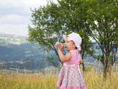 Baby with bottle on the grass — Foto de Stock