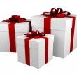 Three white gift boxes with red ribbon — Stock Photo