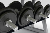 Row of metal dumbbells on support — Stock Photo