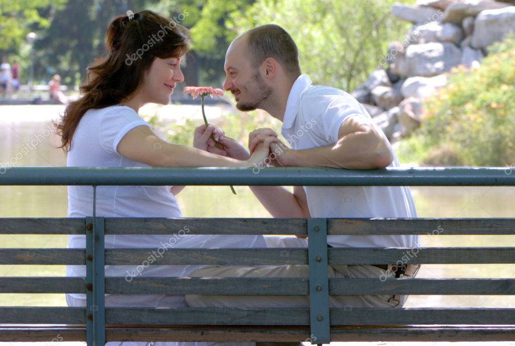 Happy married couple sitting on a bench in park — Stock Photo #1779205
