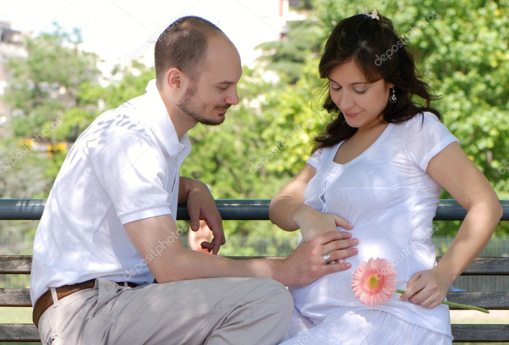 Happy married couple sitting on a bench in park — Stock Photo #1779466