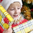 Small Santa Klaus with gifts in hands - Stock Photo