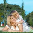Mother and son playing on green grass - Stock Photo