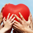 Group of hands holding heart - Stock Photo