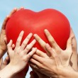 Group of hands holding heart — Stock Photo