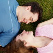Young, a loving couple lying on a grass — Stock Photo
