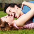 Happy young couple playing at park — Stock Photo