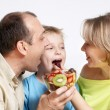 Happy family with fruit salad — Stock Photo
