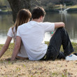 Young pair sitting on the bank of lake — Stock Photo