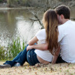 Young pair sitting on bank of lake — Stock Photo