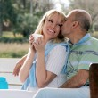 Happy couple on a bench in park — Stock Photo