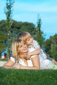 Mother and son playing on green grass — Stock Photo