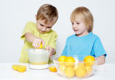 Children squeeze out orange juice — Stock Photo