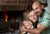 Couple near a fireplace — Stock Photo