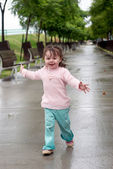 Girl running on wet avenue after a rain — Stock Photo