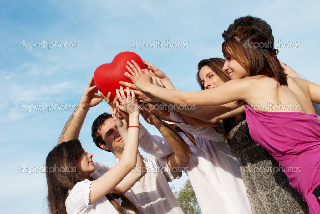 Group of young guys and girls with a sphere in the form of heart — Stock Photo #1950182