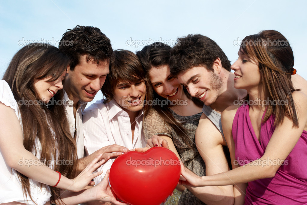Group of young guys and girls with a sphere in the form of heart — Stock Photo #1950184
