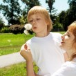 Mother with the son with dandelions — Stock Photo