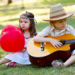 Couple with guitar on grass in park — Stock Photo