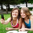Royalty-Free Stock Photo: Two girlfriends in park with a mobile phone