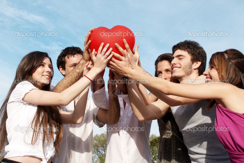 Group of young guys and girls with a sphere in the form of heart — Stock fotografie #2330054