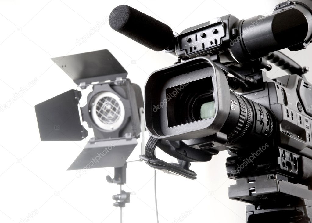 Isolated digital video camera recorder on tripod  and spot light with white background — Stock Photo #1705834