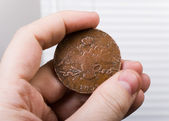 Old coin in hand — Stock Photo