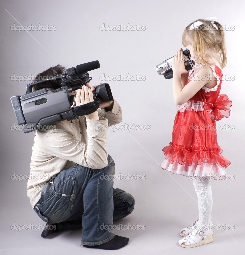 Professional cameraman and little girl with home video camera shooting one another — Photo #1862589