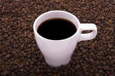 Cup in the coffee beans, isolated on a w — Stock Photo