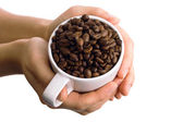 Cup with coffee beans in the hands — Stock Photo