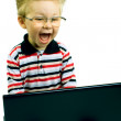Shocked young boy with  computer - Stock Photo
