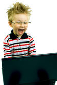 Shocked young boy with computer — Stock Photo