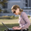 Woman working over a laptop computer — Stock Photo