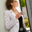 Business woman drinks coffee near window — Stock Photo
