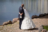 Groom and bride on coast of river — Stock Photo
