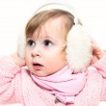 Little girl in fur headphones — Stock Photo
