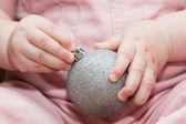 Child holding silver christmas ball — Stock Photo